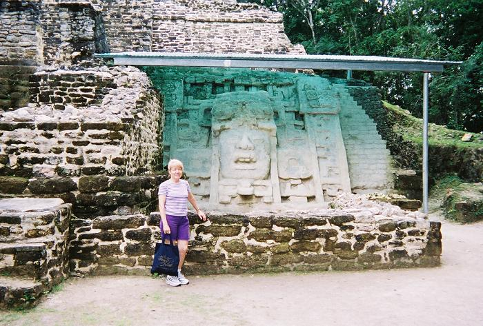 Mary standing in front of the Mask location on the right hand side of the Maya Runin of Lamanai in Belize